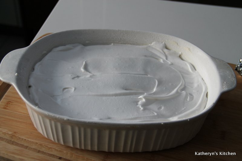 Meringue Spread out in Buttered and Icing Sugar Dusted Baking Dish